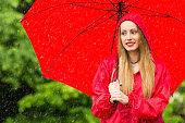 istock Woman with umbrella having fun in rainy day 1055873150