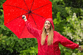 istock Woman with umbrella having fun in rainy day 1057519362