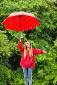 istock Woman with umbrella having fun in rainy day 1058231956