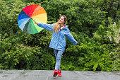 istock Woman with umbrella having fun in rainy day 1061188932