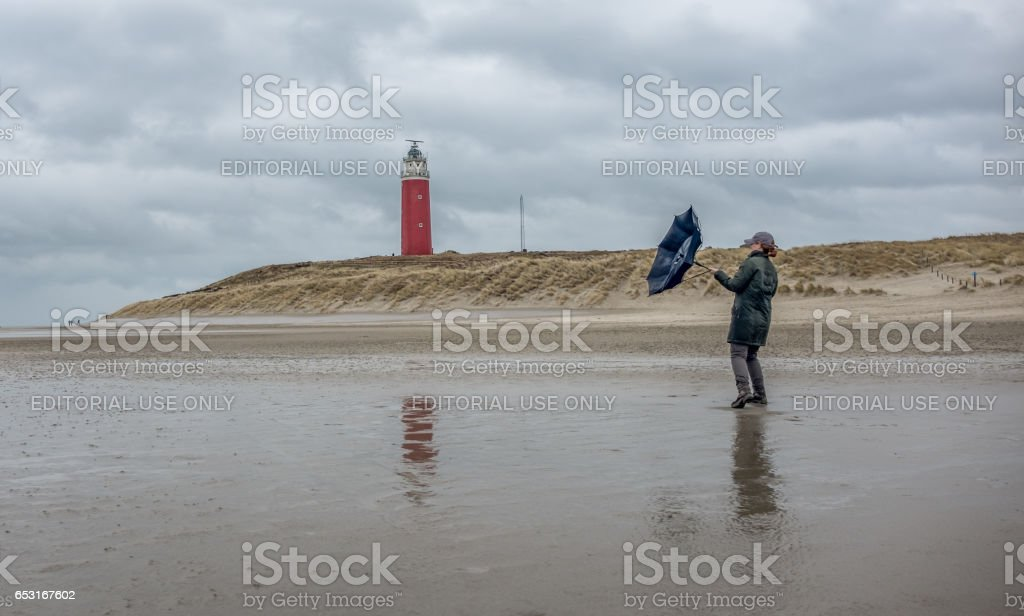 Woman with umbrella in stormy weather stock photo