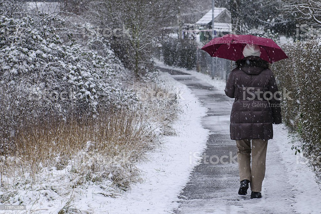 Woman with umbrella is strolling on a footpath royalty-free stock photo