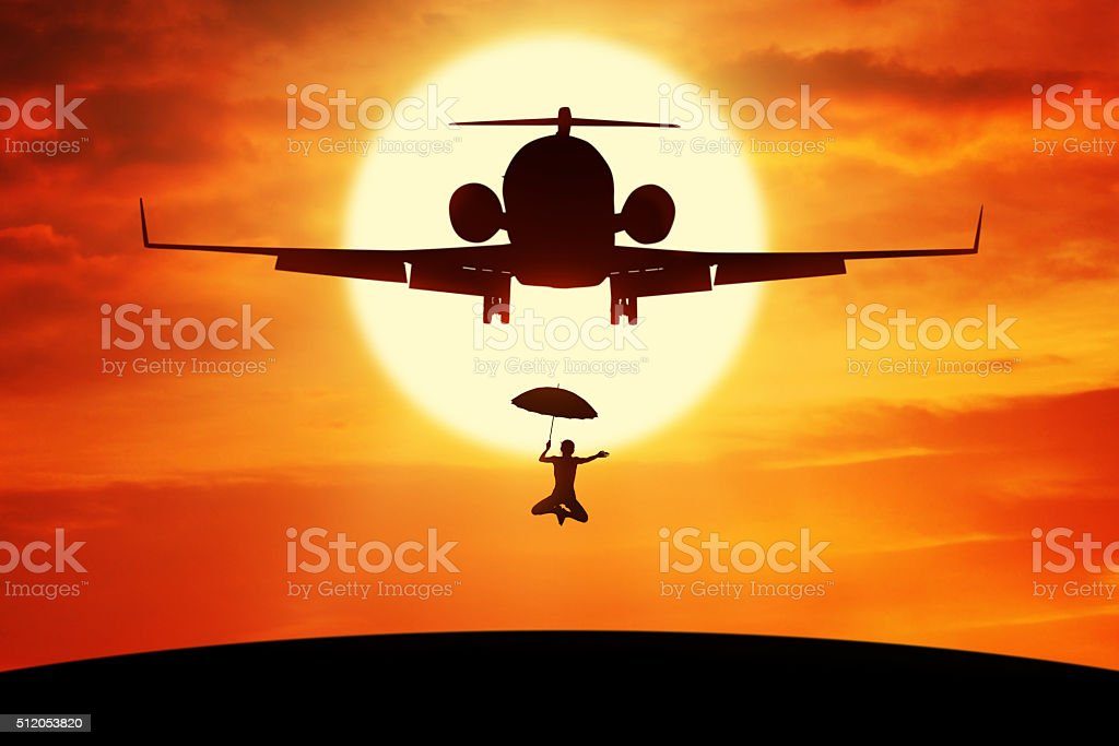 Woman with umbrella jumping under plane stock photo