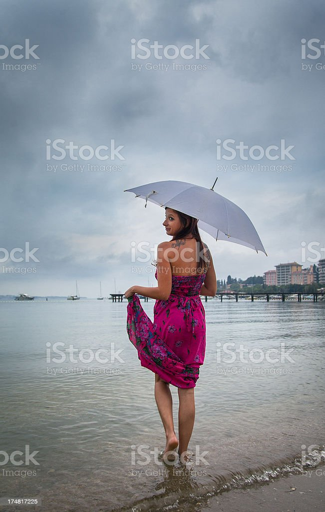 Woman with umbrella standing in the sea on rainy day stock photo