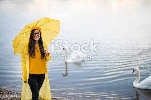 Beautiful woman with yellow umbrella in raincoat standing near lake and swan