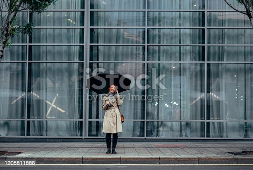 Young Caucasian ginger woman standing outdoors holding umbrella and talking on cell phone.