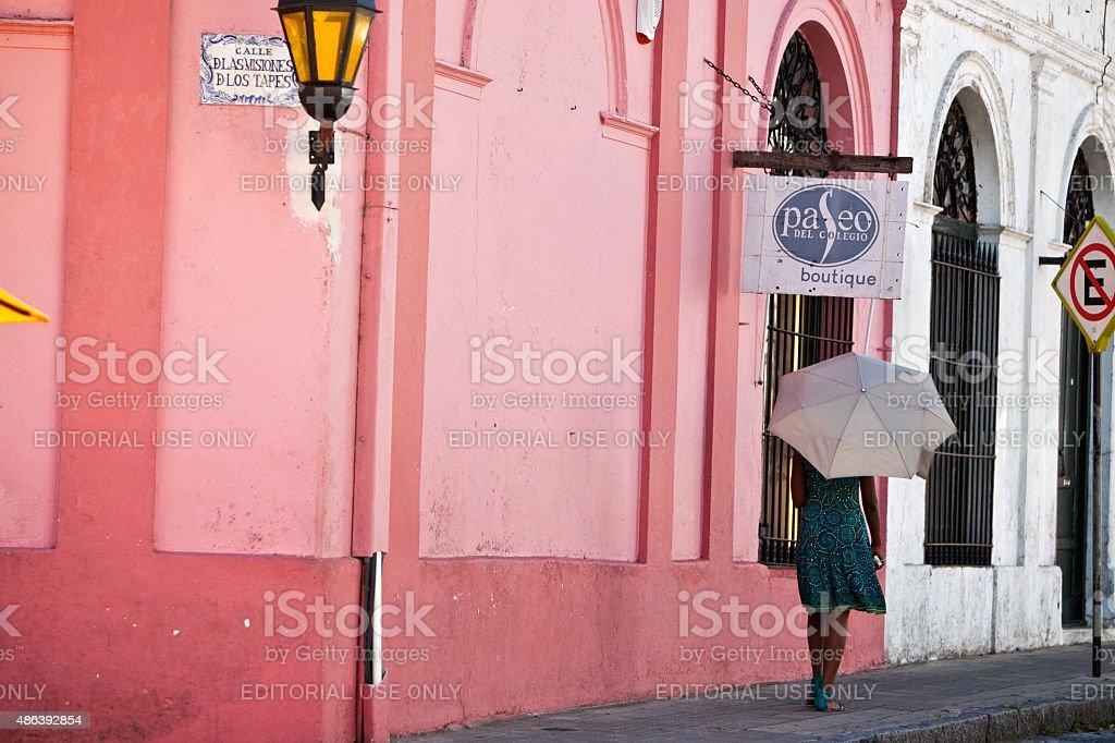 Mulher com guarda-chuva caminhando na rua Colonia Del Sacramento, Uruguai foto royalty-free