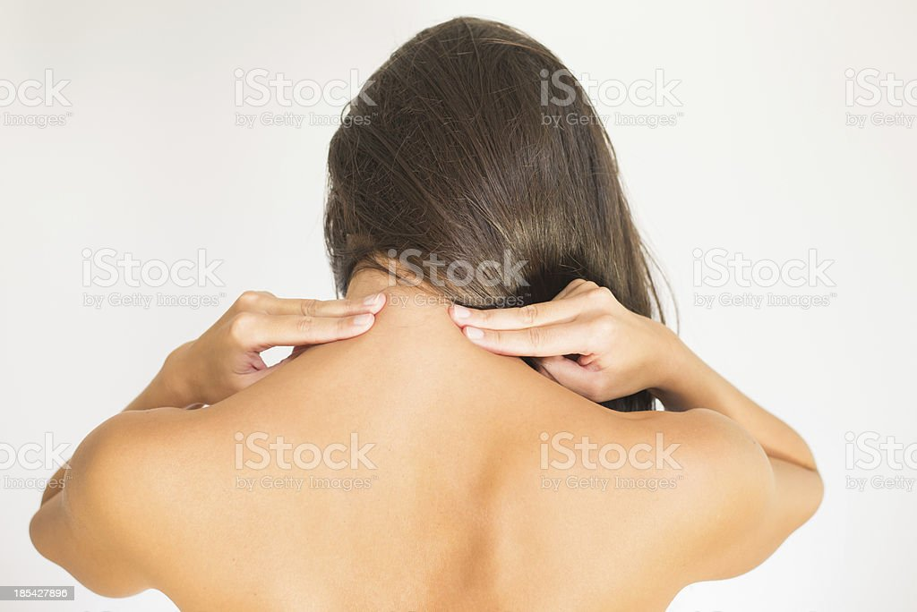 Woman with upper back and neck pain standing naked with her back to...