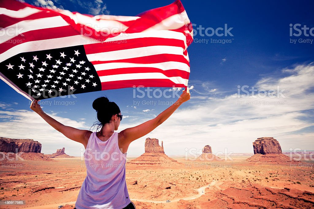 Woman with US Flag at Monument Valley, USA Landmark stock photo