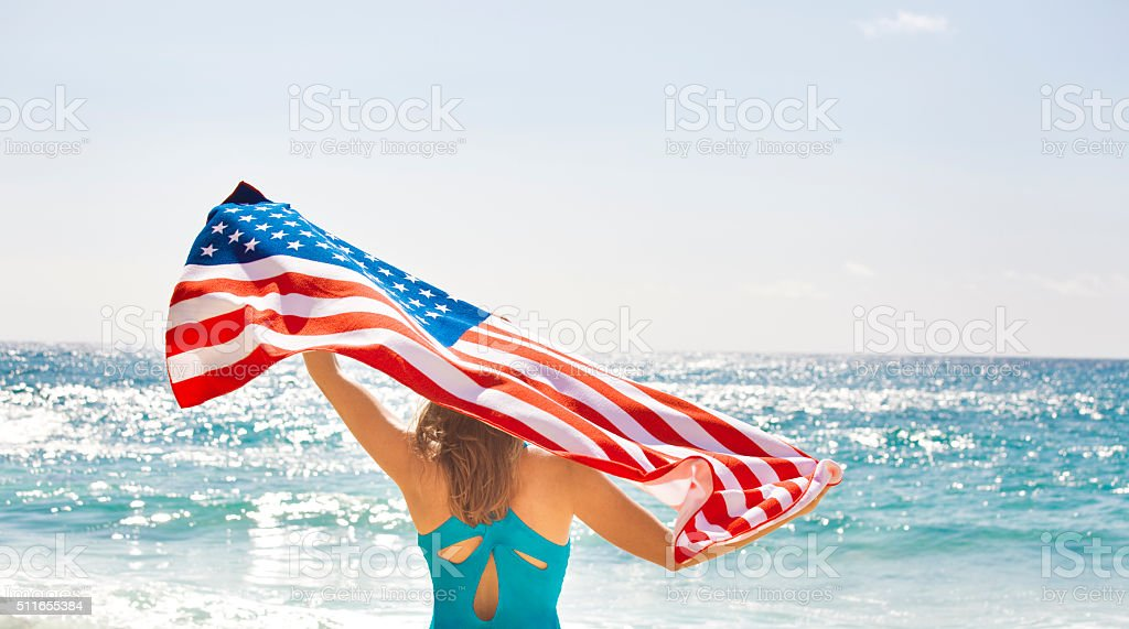 Woman with U.S. Flag for Fourth of July on Beach stock photo