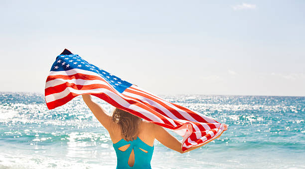 Woman with U.S. Flag for Fourth of July on Beach A young woman waving the U.S. flag on a tropical beach vacation on Fourth of July. The national banner is displayed for the Fourth of July, Memorial Day, and other national holidays and events. Photographed in horizontal format with copy space on location in Kauai, Hawaii, USA. happy 4th of july photos stock pictures, royalty-free photos & images