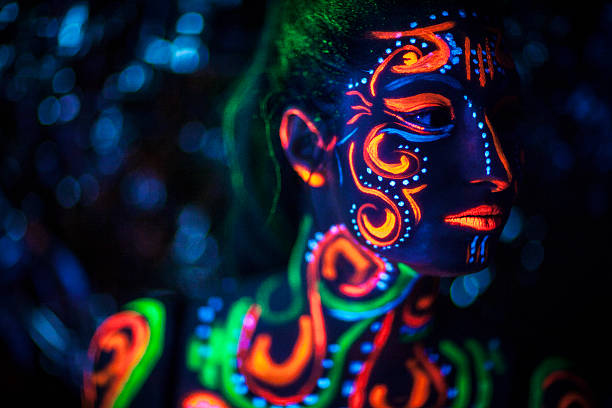 Woman With UV Bodypainting Portrait of a young woman with fluorescent ethnic bodypainting that glows in UV light body paint stock pictures, royalty-free photos & images