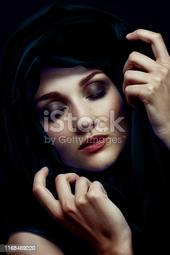 beautiful young woman with black velvet headscarf over her face, closed eyes, luxury makeup