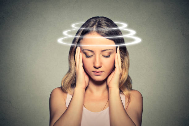 Woman with vertigo. Young female patient suffering from dizziness. stock photo