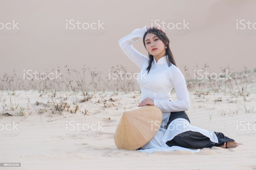 woman with Vietnam culture traditional dress on sandune during sunset ,traditional costume ,Muine Vietnam zbiór zdjęć royalty-free