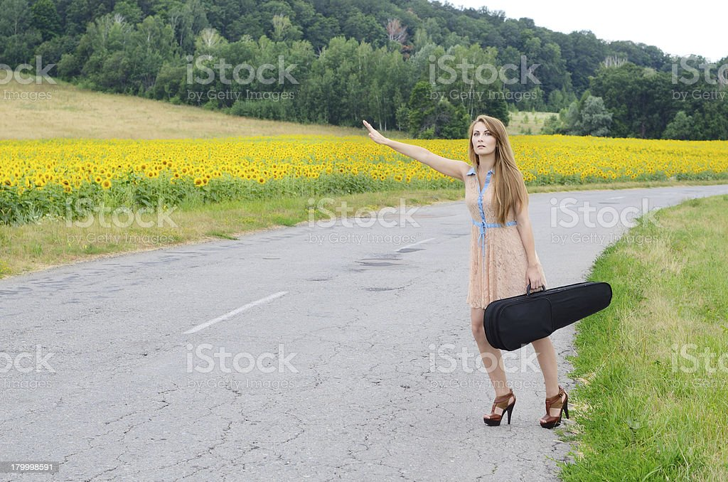 Woman with vilolin case by country road stock photo