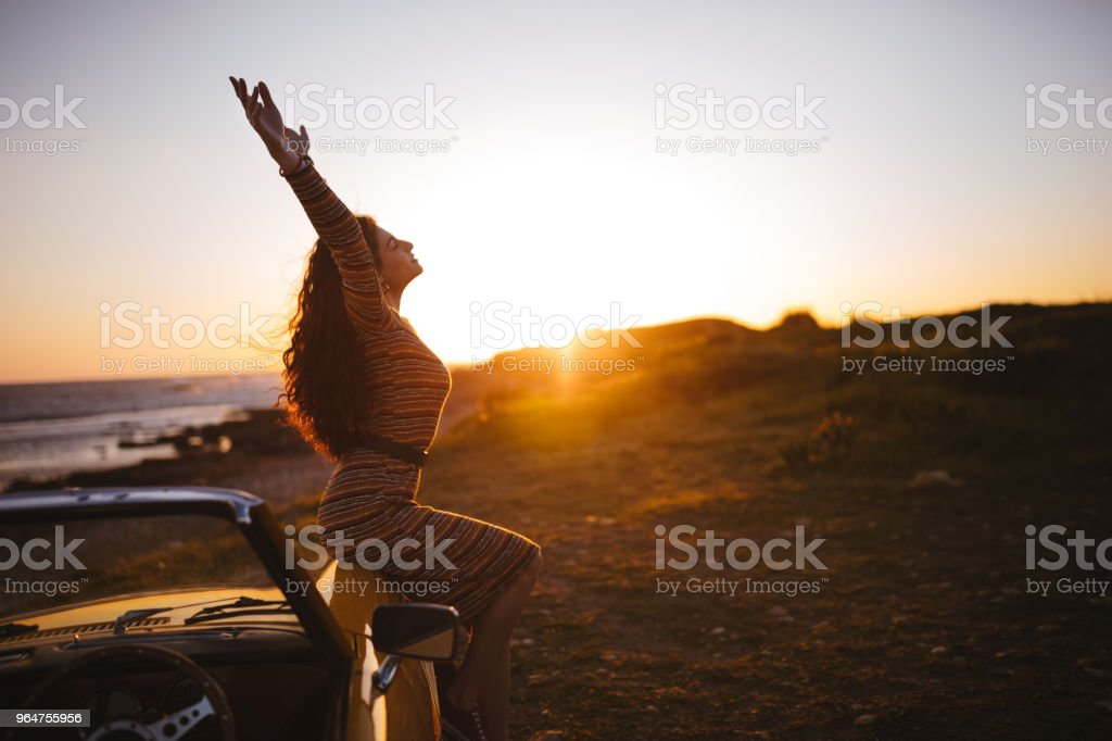 Woman with convertible car relaxing at the beach at sunset royalty-free stock photo