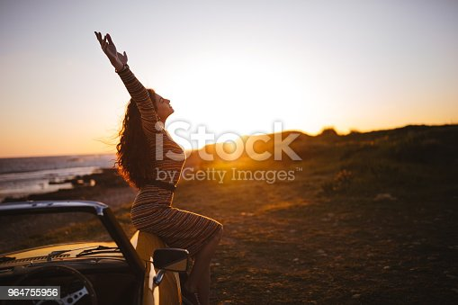 147878016 istock photo Woman with convertible car relaxing at the beach at sunset 964755956