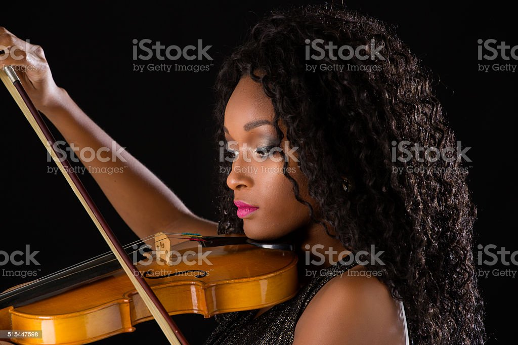 Woman with violin in dark room stock photo