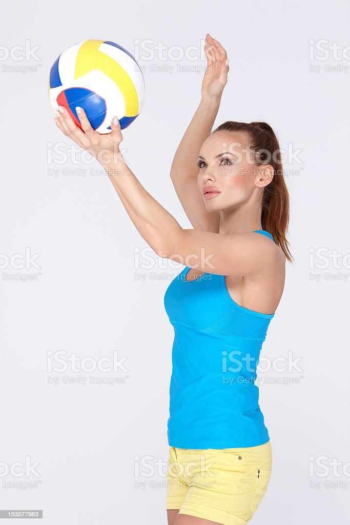 Beautiful and sporty woman holding volley ball