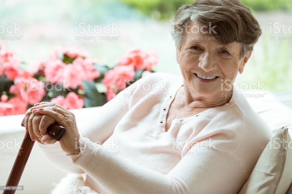 Frau mit Gehstock lächelnd – Foto