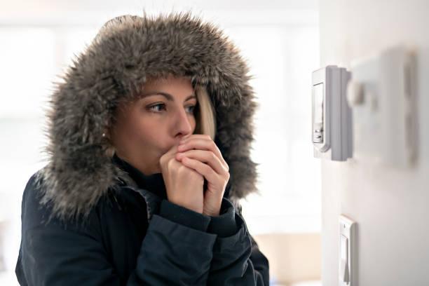 mujer con abrigo, sintiendo el frío dentro de casa - frío fotografías e imágenes de stock