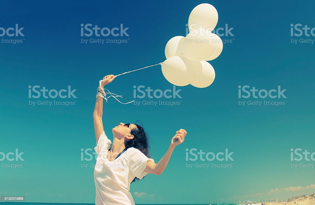 woman with white balloons stock photo
