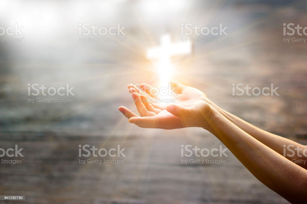 Woman with white cross in hands praying for blessing from god on...