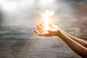 istock Woman with white cross in hands praying for blessing from god on sunlight background, hope concept 941232730
