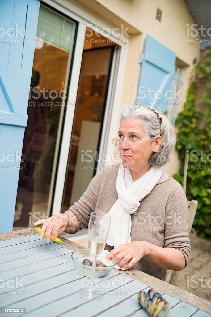 Woman with white hair opening oysters outdoors. – Foto
