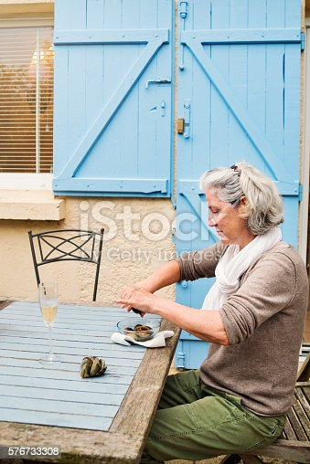 Middle-age woman with white hair is opening oysters outdoors, She is sitting alone at a table on a terrace, a white wine glass in front of her.  Vertical waist up shot with copy space. This was taken in France.