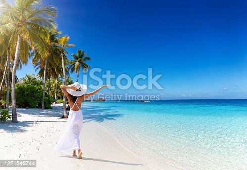 A tourist woman with white hat walks down a tropical paradise beach with palm trees, fine sand, turquoise sea and copy space in the sky