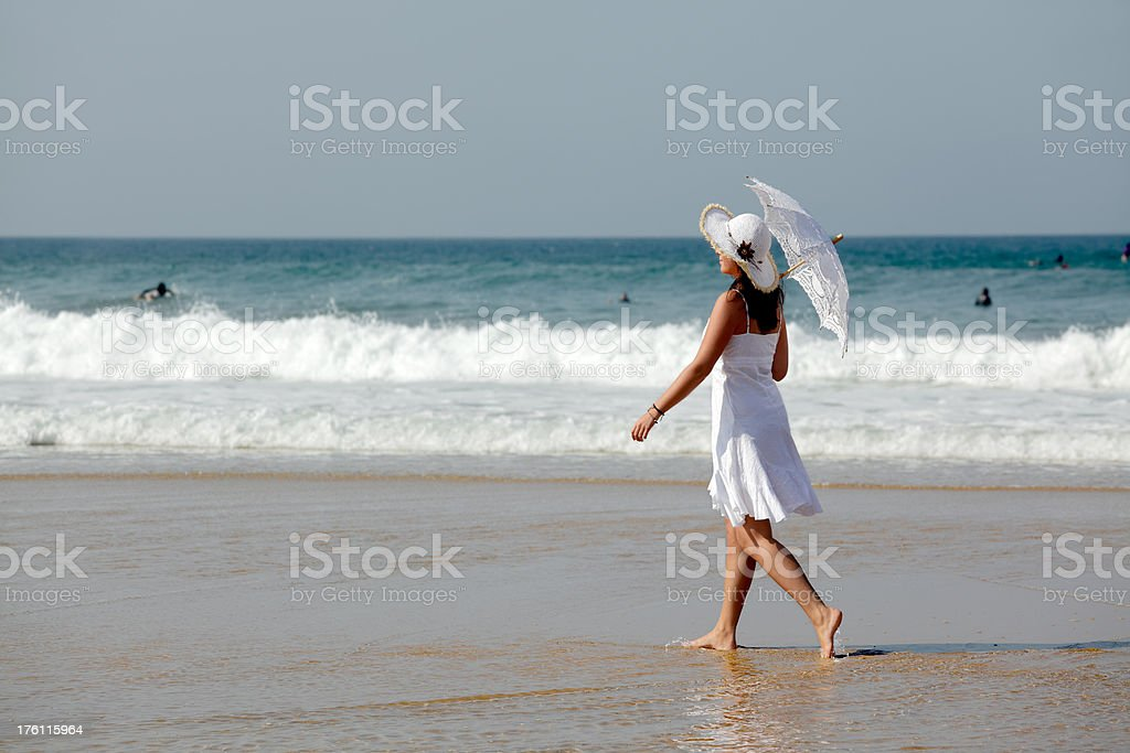 Woman with white parasol walking barefooted on beach (XXL) royalty-free stock photo