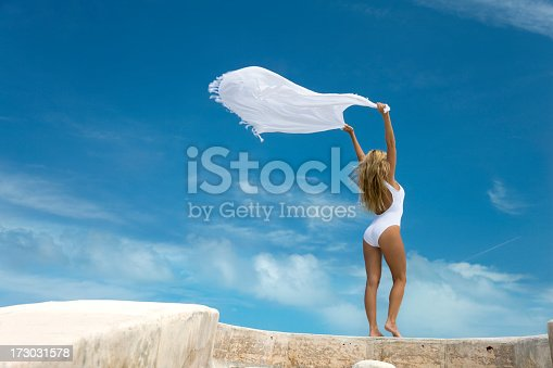 blond woman with a white sarong overhead blowing in the wind