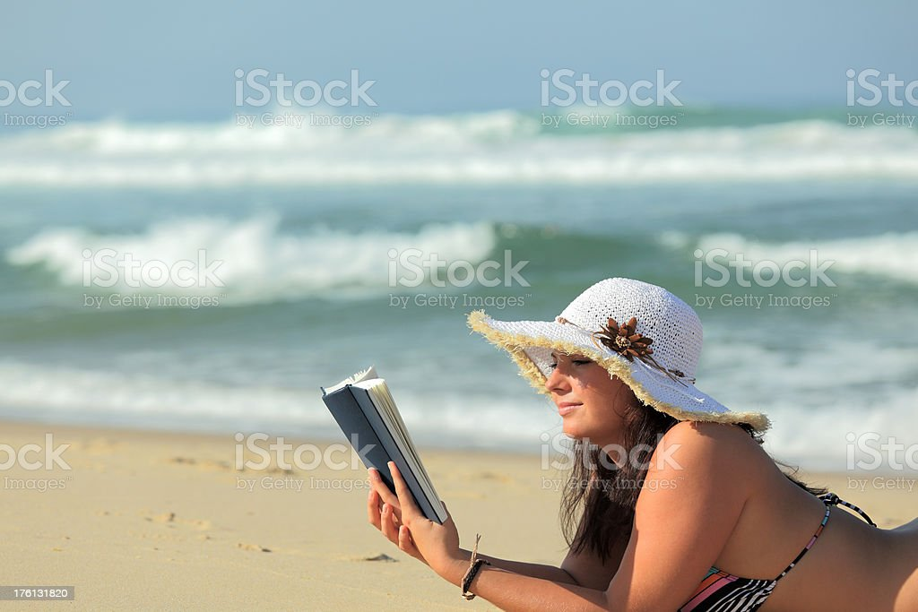 Woman with white sun hat tanning on beach reading book royalty-free stock photo