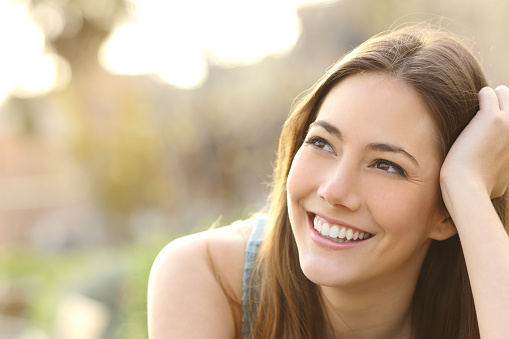 Woman with white teeth thinking and looking sideways stock photo