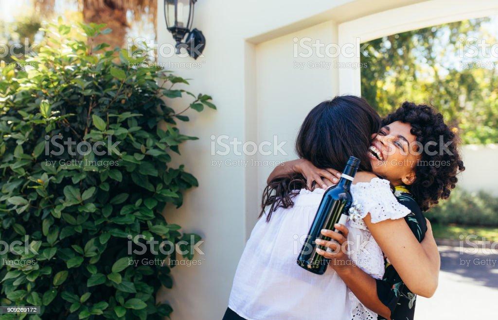 Mujer con amigo felicitando a botella de vino para casa nueva - foto de stock