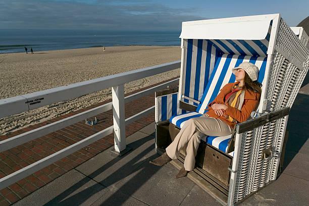 frau mit winterkleidung entspannen sie im liegestuhl am meer (xxl - sylt urlaub stock-fotos und bilder