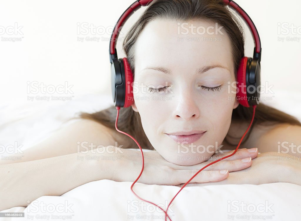 Woman with wired headset relaxing on bed stock photo