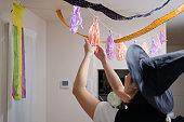ハロウィンの飾りを飾る魔女帽子の女