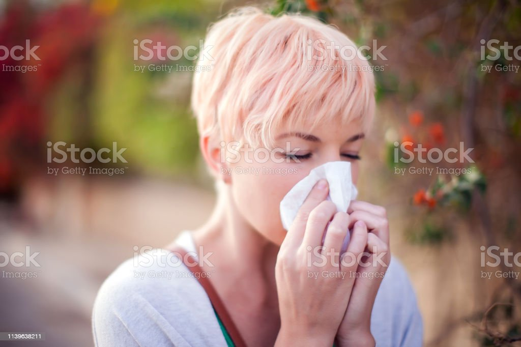 Woman with with allergy symptom blowing nose. Health care and medical...