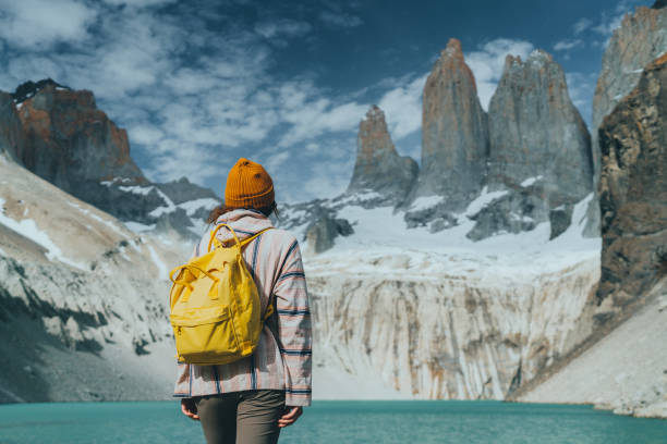 Woman with yellow backpack looking  at scenic view of Torres del Paine National Park stock photo