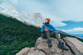 Young Caucasian woman with yellow backpack looking  at scenic view of Torres del Paine National Park in Chile