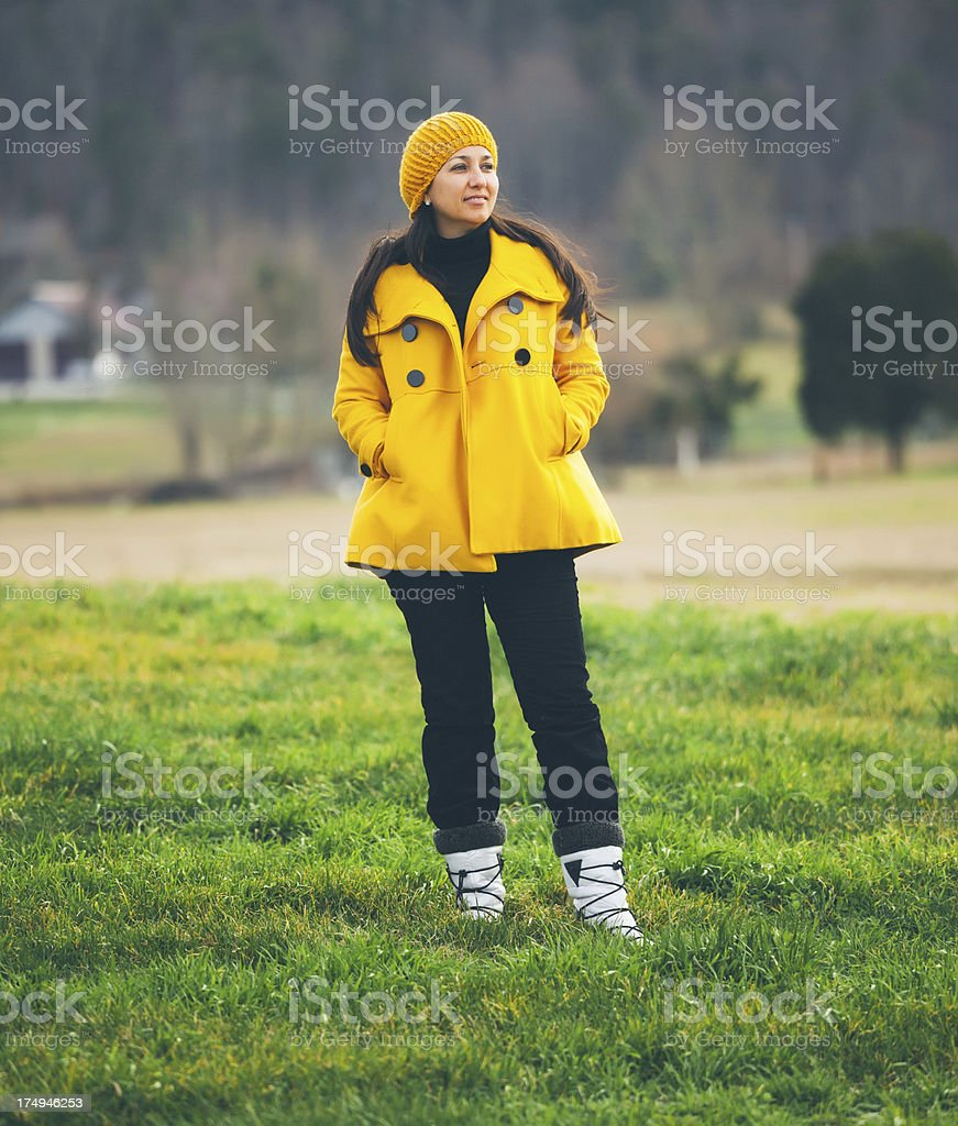 woman with yellow coat in a field royalty-free stock photo