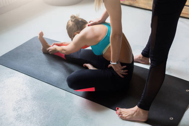 Woman with yoga instructor in class, sit forward bend pose Yoga class instructor helps beginner to make asana exercises. Teacher assists to make sit forward bend pose, Pashimottanasana. Healthy lifestyle in fitness club. Stretching with coach yoga instructor stock pictures, royalty-free photos & images