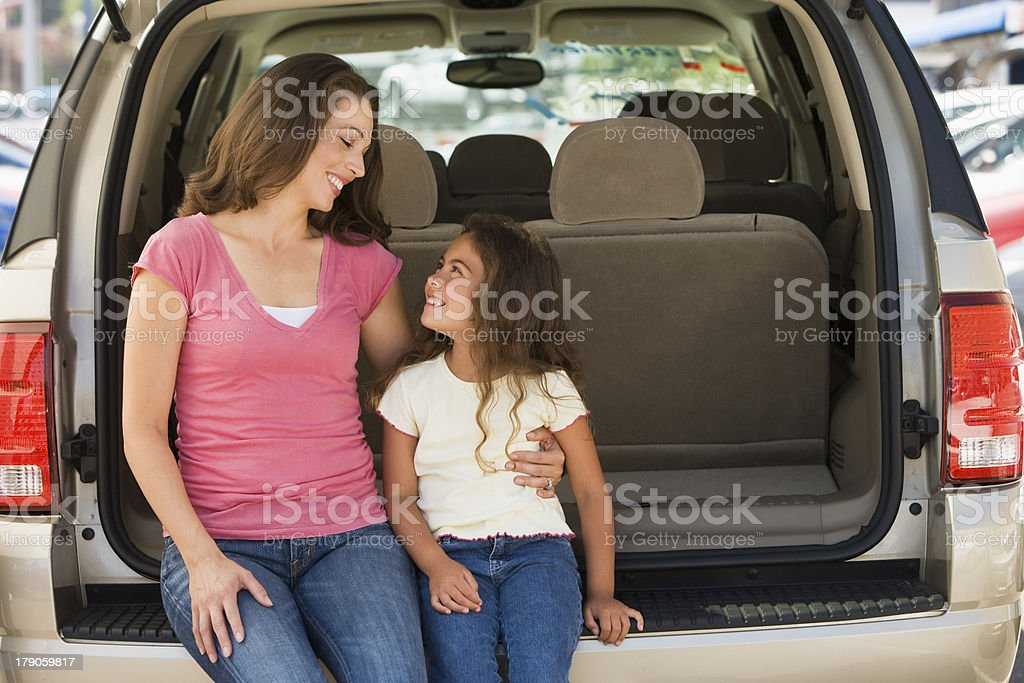 Woman with young girl sitting in back of van smiling royalty-free stock photo