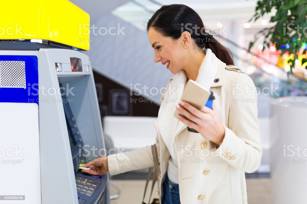 Woman withdrawing cash at an ATM stock photo
