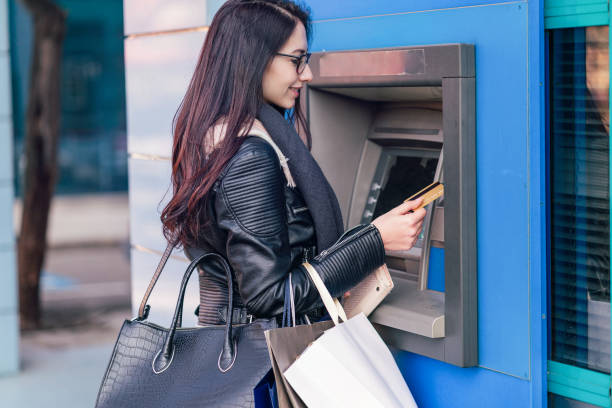 Woman withdrawing cash from ATM stock photo