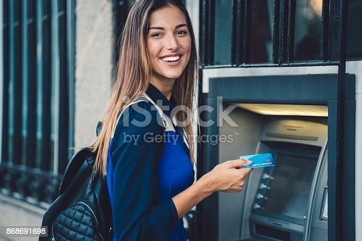 istock Woman withdrawing money at the ATM 868691698
