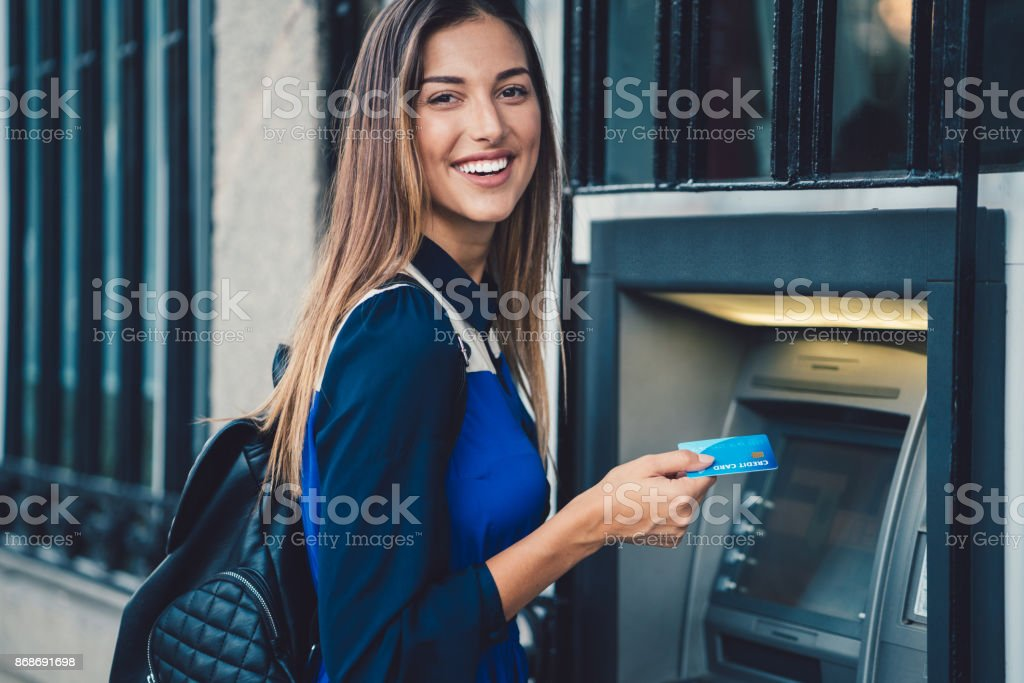 Woman withdrawing money at the ATM stock photo